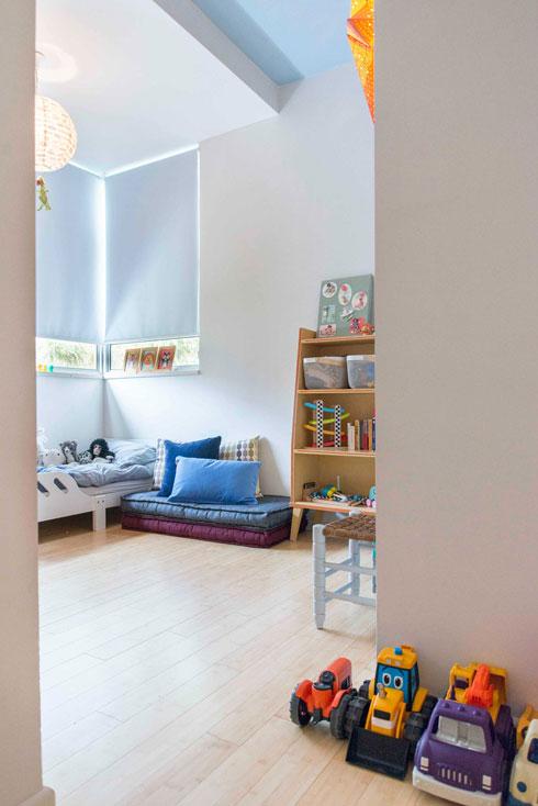 התקרה המונמכת בחדרו של הבן מגדירה את אזור השינה. התקרה מעל אזור המשחק נצבעה בתכלת (צילום: גל דרן)