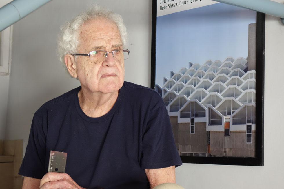 """אדריכל משה גיל. בילדותו הוא נקרא קורט גולץ וכלל לא ידע עברית.  """"הייתי ילד ולכן לא הרגשתי את איום המוות"""", הוא אומר על תקופת מלחמת העולם השנייה, """"אבל הוא היה שם"""". על הקיר צילום מבנה ספריית ארן שתכנן באוניברסיטת בן גוריון בבאר שבע (צילום: מיכאל יעקובסון)"""