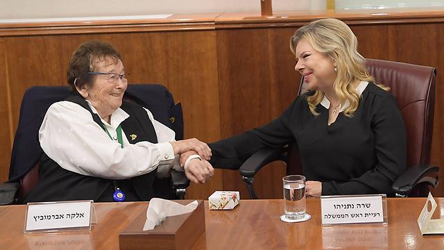 Survivor Elka Abramovitz holds Sara Netanyahu's hand (Photo: Amos Ben Gershom/GPO)