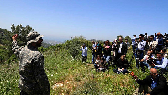 Hezbollah officer giving press a tour of the border