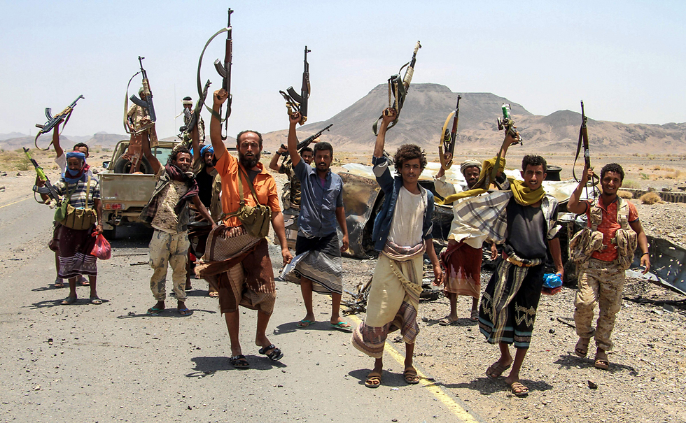 לוחמים תימנים הנאמנים לנשיא הפרו-סעודי מניפים את נשקם. מלחמת האזרחים בתימן נמשכת כבר יותר משנתיים (צילום: AFP)