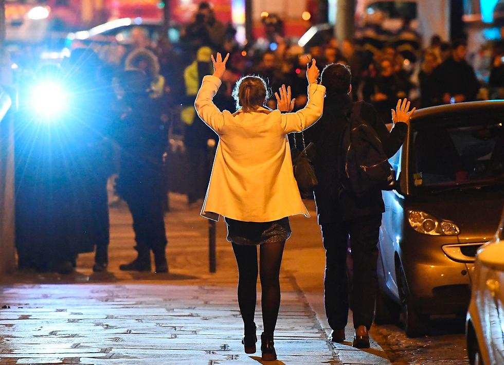 אזרחים תמימים מרימים ידיים לפני שוטרים ליד זירת הפיגוע בשאנז אליזה, פריז (צילום: AFP)