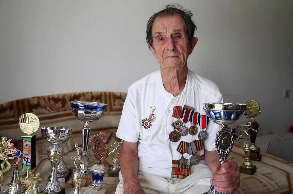 סימקין עם גביעים מתחרויות הריצה (צילום: עמית שאבי) (צילום: עמית שאבי)