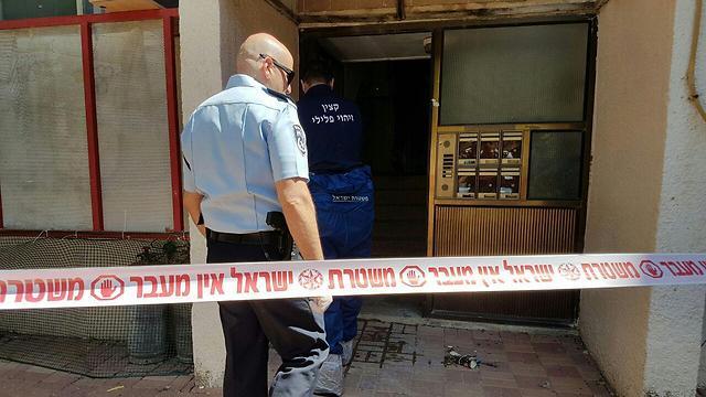 חוקרים בפתח הבניין שבו אירע הרצח (צילום: דוברות המשטרה) (צילום: דוברות המשטרה)