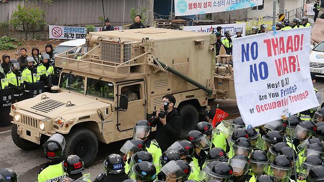 """משאיות הובילו את חלקי המערכת על רקע מחאה """"לא ל-THAAD, לא למלחמה"""" (צילום: EPA) (צילום: EPA)"""