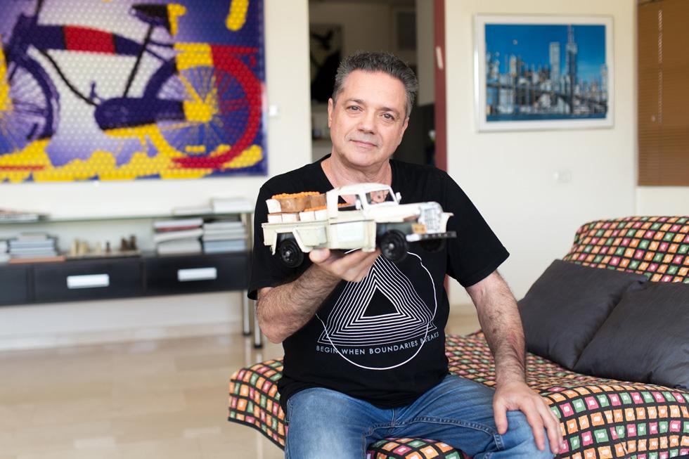 """דייויד סלע בביתו בתל אביב, עם דגם של רכב ישן. """"הישראלים חוזרים למקום שזכור להם כמחבק ונעים"""" (צילום: אלון פרס)"""