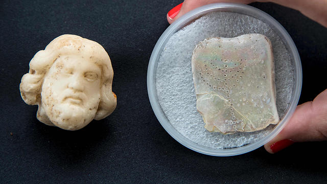 Head part of a figurine (L) from the Roman period depicting the Asclepius, god of medicine and a small tablet engraved with a seven-branched menorah (Photo: AFP)