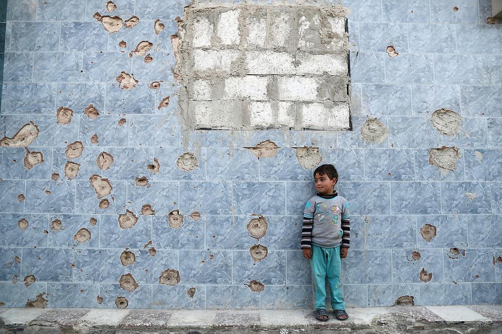ילד סורי עומד ליד קיר מנוקב בכדורים בעיר דומא, פרבר של דמשק שנחשב למעוז של המורדים (צילום: AFP)