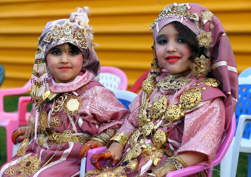 ילדות בבגדים מסורתיים באירוע של בית ספר בשכונת טאג'ורה שבטריפולי, בירת לוב (צילום: AFP)