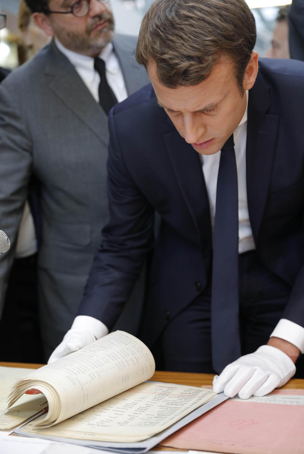 Macron looks at archive documents in the memorial. (Photo: Reuters)