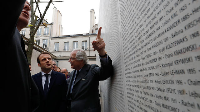 Macron listens to Chairman of the Shoah Memorial, Eric de Rothschild (R), as they walk by the Wall of the Names, on which are engraved the names of 76,000 Jews, including 11,000 children, who were deported from France during the WWII Nazi occupation. (Photo: AFP)