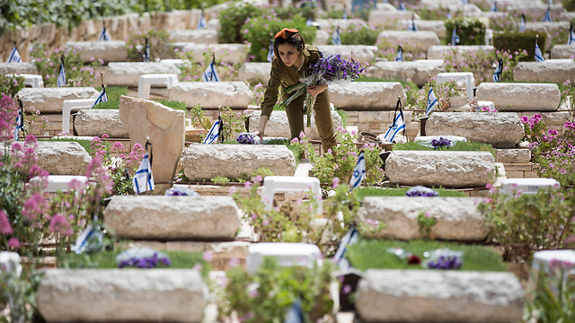 Soldier lays flowers on graves of fallen soldiers on Mount Herzl (Photo: EPA) (Photo: EPA)