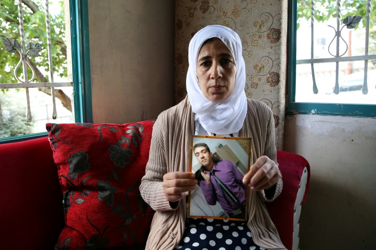 Manal al-Saayed, the mother of Hamas captive Hisham al-Sayed, holds a picture of her son (Photo: AFP)