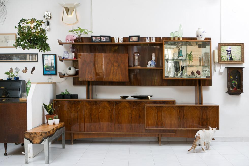 שידת העץ נמצאה באתר ''אגורה''. כמו הקירות והרהיטים האחרים בבית, היא משמשת כבמה לאוסף הפריטים של בני הזוג - עבודות אישיות ושל קולגות וחברים. ''אנחנו אגרנים'', הם מודים. ''אנחנו נתקלים בדברים בחיים המקצועיים שלנו ואוספים אותם, וגם אם עכשיו הם לא מתאימים לנו, אנחנו שומרים'' (צילום: שירן כרמל)