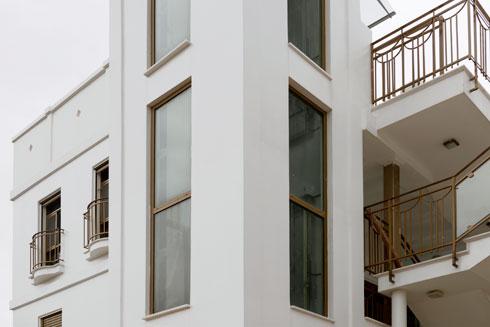 הגוון לבן בוהק, פתחי החלונות גבוהים במיוחד, והתריסים מוזהבים (צילום: גדעון לוין)