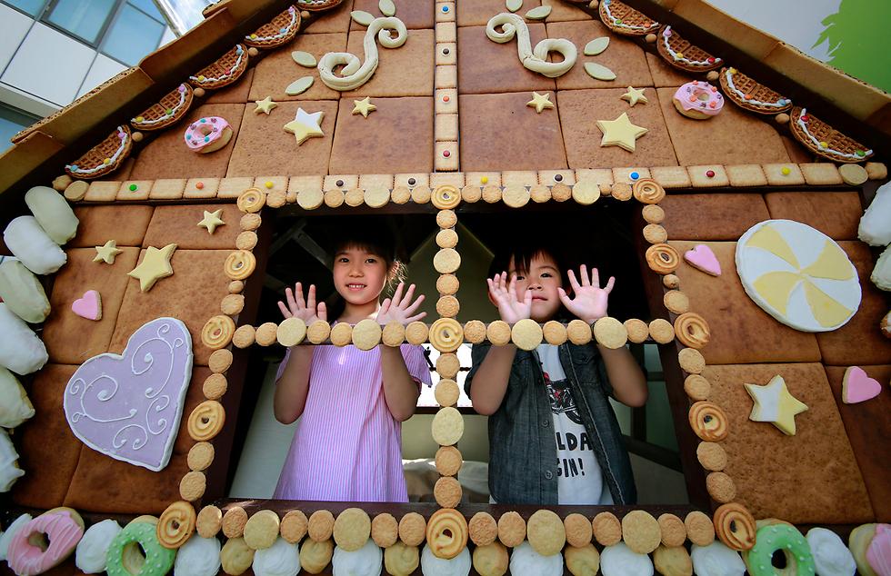 ילדים מציצים מתוך בית שנבנה כולו מממתקים בטוקיו, בירת יפן. הבית מתנשא לגובה של שלושה מטרים והוא מורכב מ-2,000 חתיכות עוגה, שוקולד, עוגיות ולחם (צילום: AP)