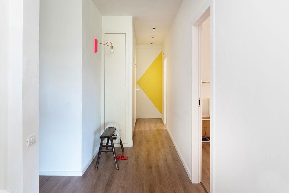 המסדרון שלאורכו (משמאל) ארון  באורך חמישה מטרים וחצי. מימין: חדר ההורים, אחריו חדר הרחצה המשותף ובקצה הדירה חדר הילדים, שדלתו היא דלת הזזה גבוהה במיוחד. המשולש הצהוב על דלת חדר הילדים מכניס עניין ויוצר מפגש צבעוני  מקורי עם המנורה הוורודה (צילום:  גלית דויטש)