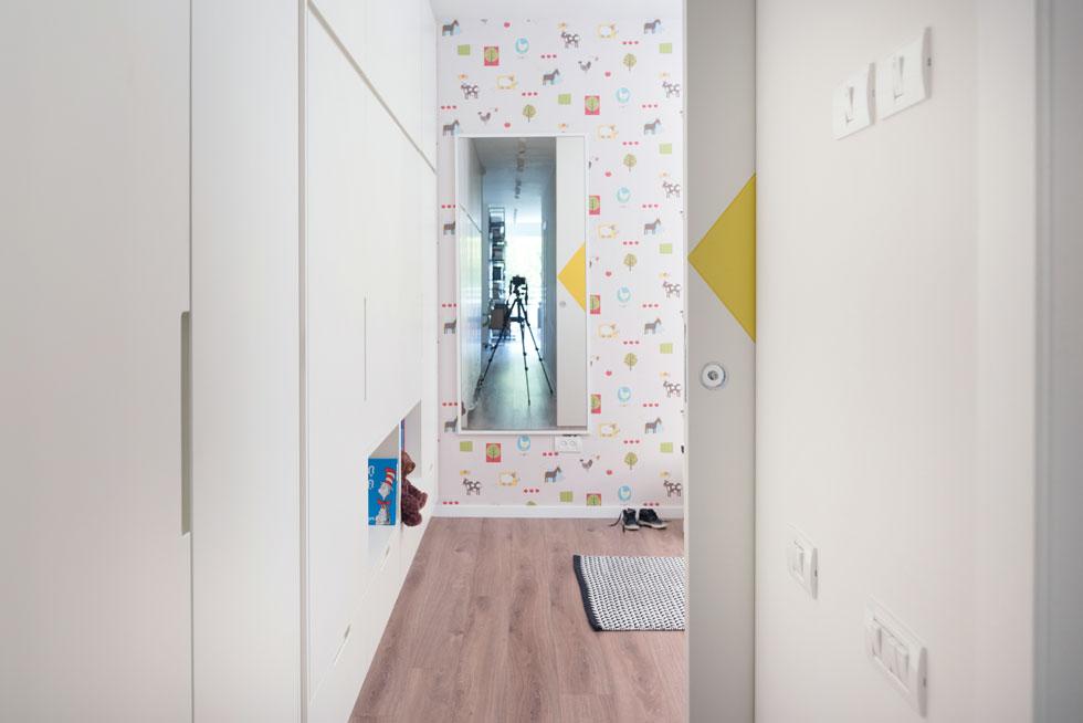 המראה בחדר הילדים תלויה על קיר מחופה בטפט צבעוני ומשקפת את הבית עד קצהו, כולל החלון שפונה אל הפארק (צילום:  גלית דויטש)