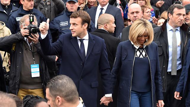 מקרון מגיע עם אשתו בריז'יט להצביע בקלפי (צילום: AFP)