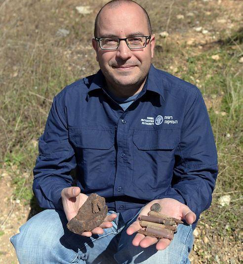 אסף פרץ עם חלק מהממצא הצבאי שהתגלה באתר (צילום קלרה עמית, רשות העתיקות)