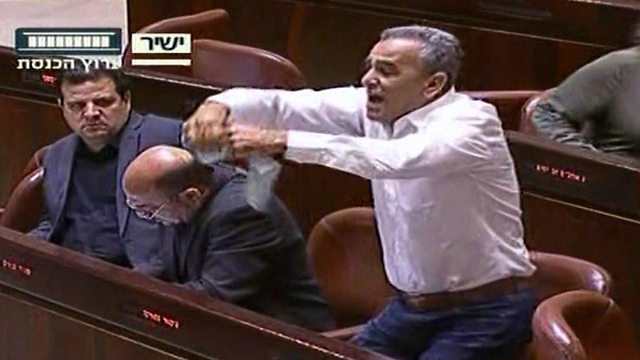 MK Zahalka tearing up the bill proposal (Photo: Knesset Channel)