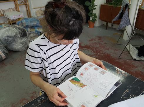 טל צור בסטודיו iota, עם ספר יפני על סריגה טורקית (צילום: ענת ציגלמן)