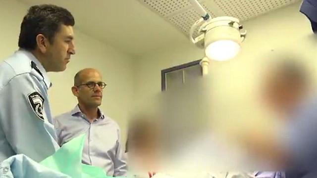 Yoram Halevy (L) visits N. in the hospital. (Credit: Israel Police)