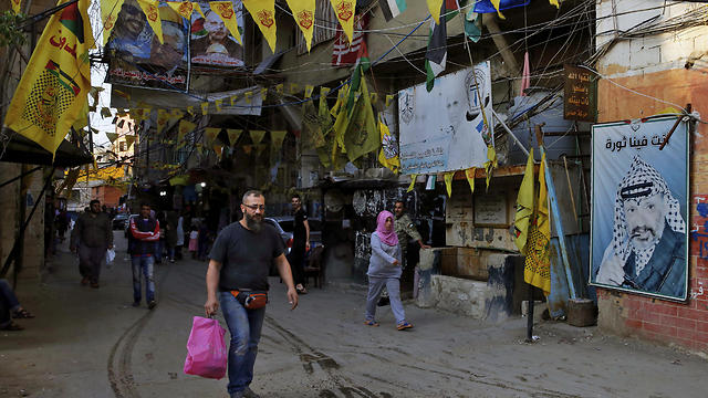 In this Thursday, May 4, 2017 photo, people walk underneath the banners of Fatah and the Palestinian flags inside the Bourj al-Barajneh Palestinian refugee camp in Beirut, Lebanon.  Palestinians in Lebanon suffer discrimination in nearly every aspect of daily life, feeding a desperation that is tearing their community apart. (Photo: AP) (Photo: AP)