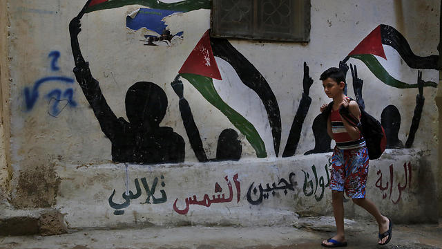 "In this Thursday, May 4, 2017 photo, a boy walks by graffiti of the Palestinian flags with Arabic reads: ""The flag is four colors that shine on the face of the sun"" in the Bourj al-Barajneh Palestinian refugee camp in Beirut, Lebanon. (Photo: AP) (Photo: AP)"