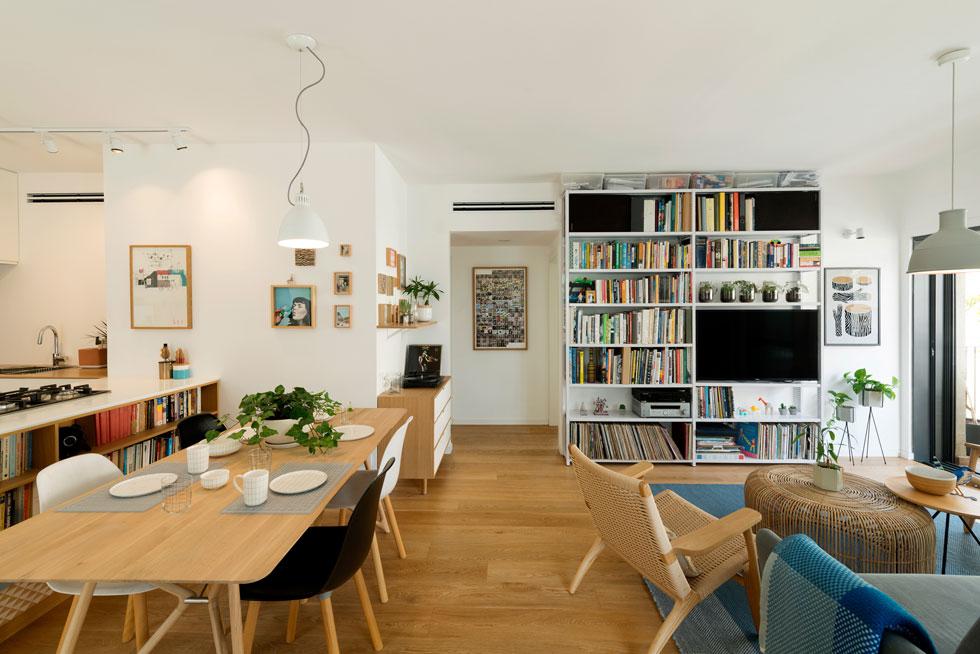 הרקע רגוע: קירות וארונות לבנים, רהיטי עץ בהירים, מסגרות תואמות ופרקט שהונח באותו כיוון בכל הדירה, ומייצר תחושה של אחידות וזרימה (צילום: גדעון לוין)