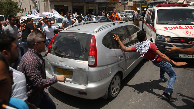 התקרית בחווארה. רכבו של היורה, האמבולנס שחסם וההמון מסביב (צילום: AFP) (צילום: AFP)