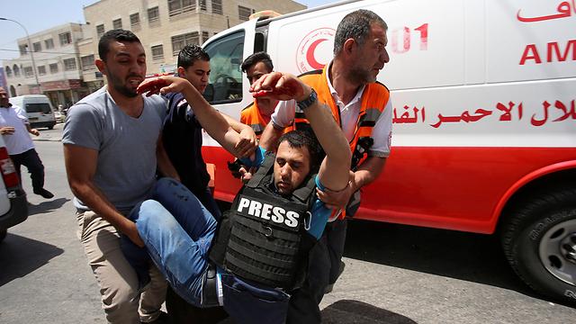 """מג'די שתייה, צלם של """"AP"""", נפצע מהירי (צילום: רויטרס)"""