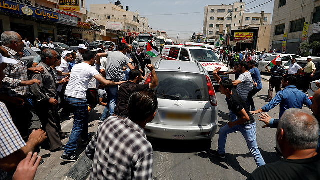 פלסטינים מתקיפים את הרכב (צילום: רויטרס)