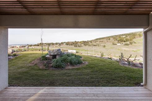 """מבט אל החצר האחורית. במרכז המדשאה """"דולמן"""", מעין שולחן אבן עתיק שרשות העתיקות דרשה לשמר (צילום: אסף אורן)"""