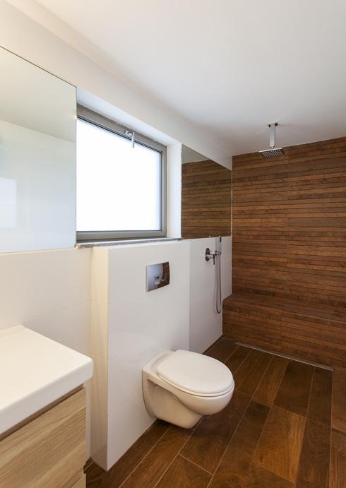 בחדרי הרחצה הרצפה והקירות מחופים באריחי קרמיקה דמויי עץ (צילום: אסף אורן)