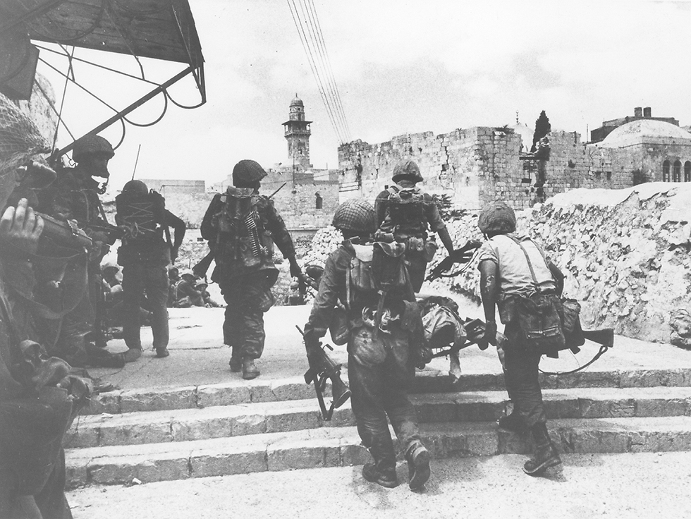 Troops carrying a wounded soldier on a stretcher. A force from the 55th Paratroopers Brigade prepares for fighting in the Old City, while evacuating the wounded