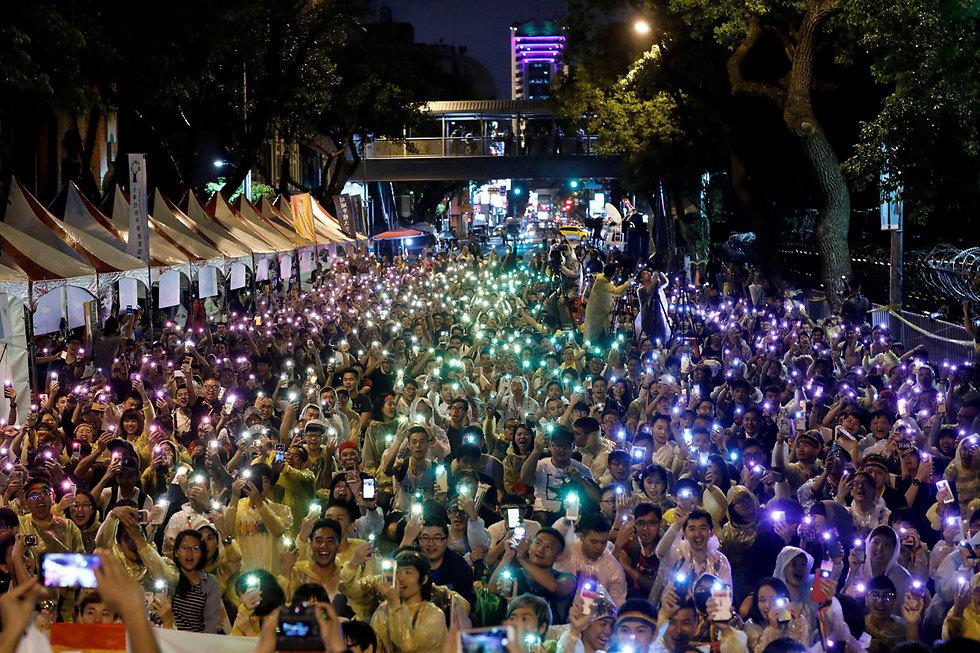 המוני אנשים בטאיפיי מאירים את הערב עם הטלפונים הניידים שלהם לאחר שבית המשפט החוקתי אישר לגליזציה של נישואים חד-מיניים (צילום: רויטרס)