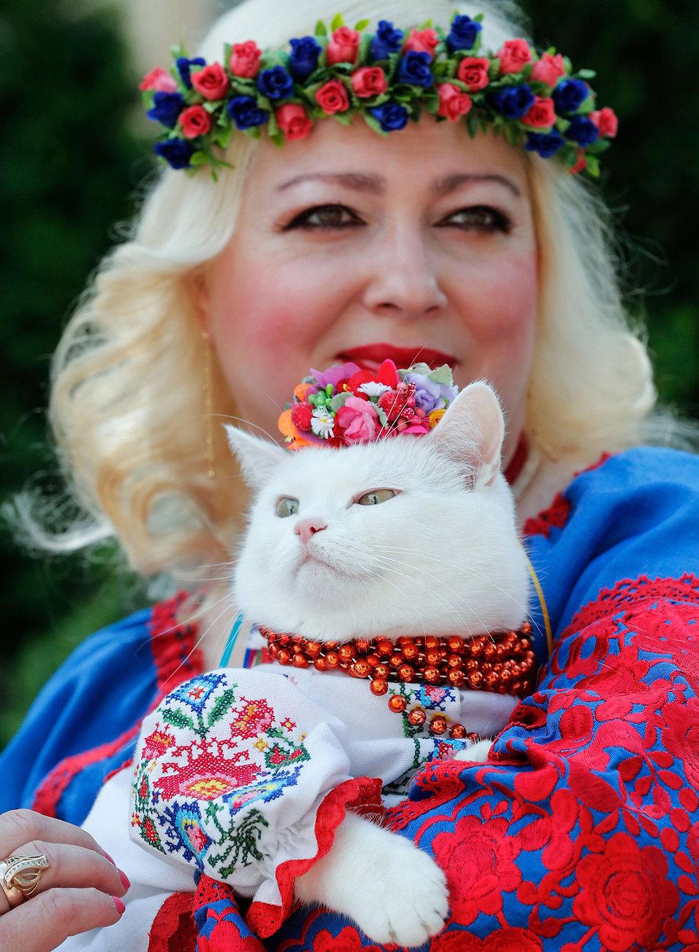 אישה אוקראינית וחתולתה לובשות בגד סלבי מסורתי בקייב שזוכה באחרונה לפופולריות גדולה במדינה (צילום: EPA)