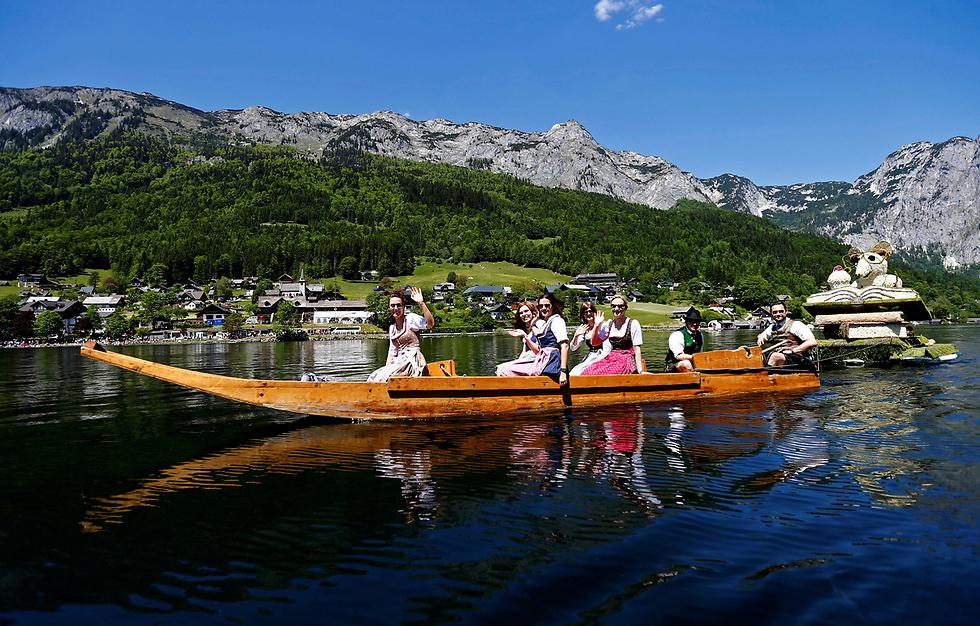 סירה שנושאת עליה דמויות מפרחי נרקיס נגררת במי אגם גרונדסלי, אוסטריה, במהלך חגיגות פסטיבל הנרקיס (צילום: רויטרס)