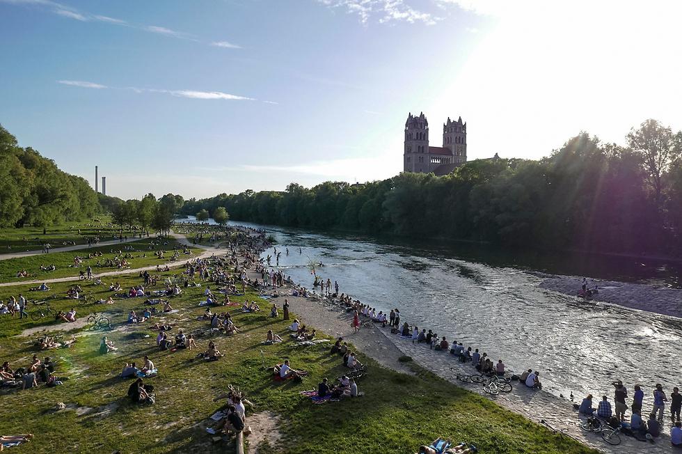 אנשים נופשים על גדות נהר איזר במינכן, גרמניה (צילום: EPA)