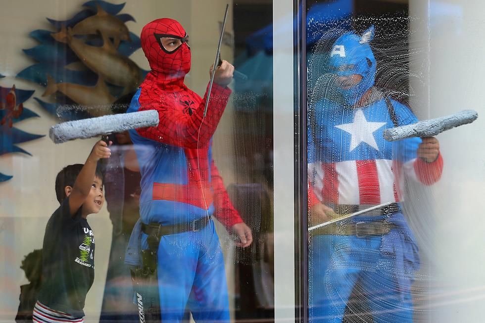 דומיניק בן הארבע עוזר לדמויות גיבורי על לנקות חלונות בבית החולים לילדים ראדי בסן דייגו (צילום: רויטרס)