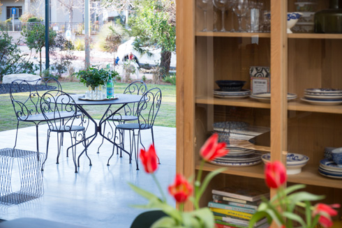 פינת ישיבה בגינה האחורית. מימין: שידת עץ שבה כלי שולחן (צילום: שי אפשטיין)