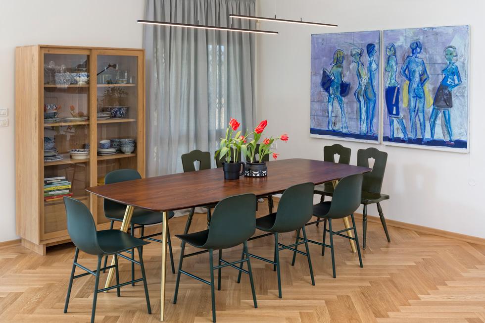 בפינת האוכל שולחן ארוך במיוחד. על הקיר שני ציורים של יוני גולד, וכלי אוכל בכחול ולבן מוצגים בארון עם דלתות זכוכית (צילום: שי אפשטיין)