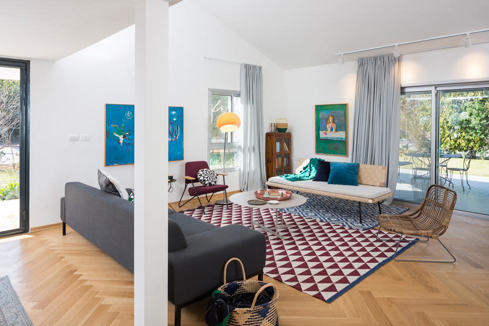בסלון שילוב של ישן וחדש, ספה מטולמנ'ס ומולה ספה מאיקאה. פרקט חדש, שטיחים וכריות מוסיפים חום וצבע (צילום: שי אפשטיין)
