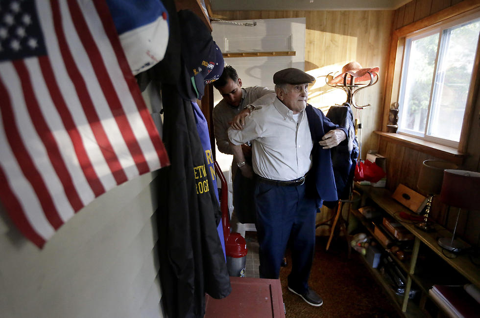 "Holocaust survivor Steve Ross, right, is helped with his jacket by his son Mike Ross, behind, as they prepare to depart Steven Ross' home in Newton, Mass., to attend the premier of the film ""Etched in Glass: The Legacy of Steve Ross."" (Photo: AP) (Photo: AP)"