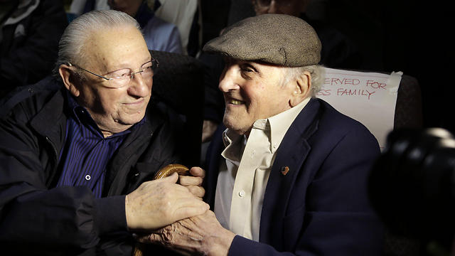 "Holocaust survivors Israel Arbeiter, left, and Steve Ross, right, greet one another at a theater before the premier of the film ""Etched in Glass: The Legacy of Steve Ross,"" in West Newton, Mass. (Photo: AP) (Photo: AP)"