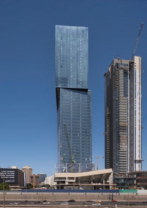 אולם הספורט על רקע מגדל המשרדים (שבנוי משתי תיבות המונחות בהסטה) ומגדל המגורים הצפוף לצדו (מעל 300 יחידות דיור) (צילום: ליאור גרונדמן)