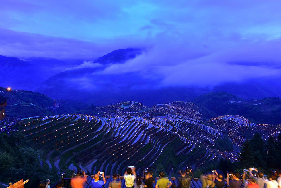 אלפי אנשים מדליקים לפידים ומתפללים לקציר טוב במהלך פסטיבל מקומי בעיר גווילין שבמחוז גואנגשי בסין (צילום: רויטרס)