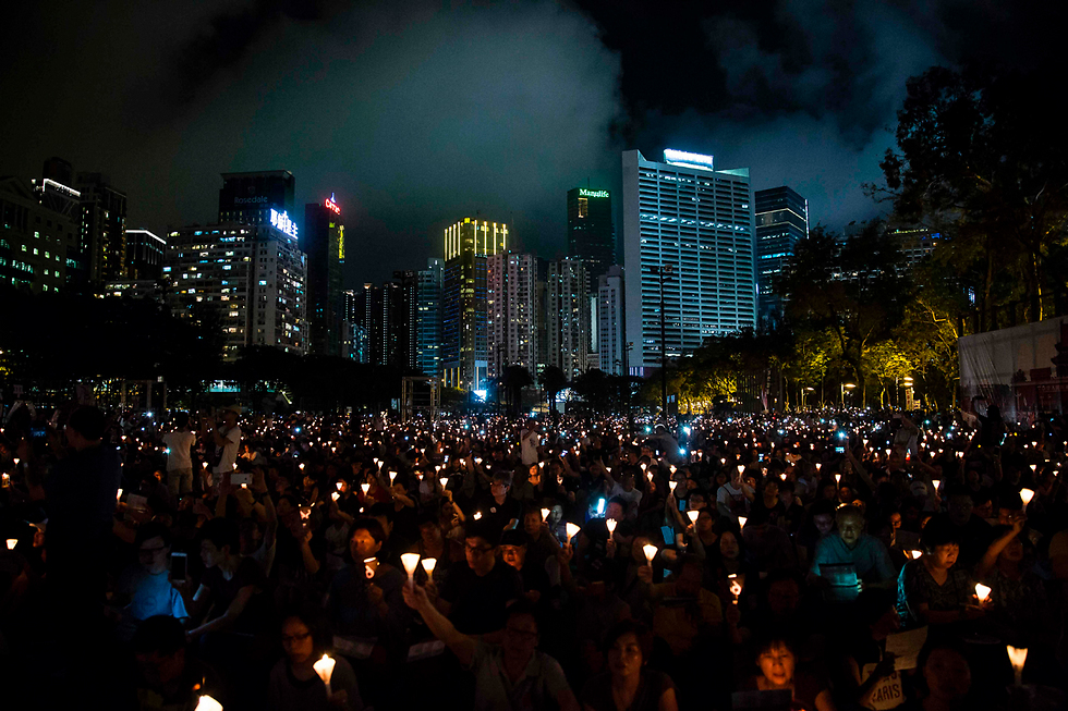 המונים בהונג קונג ציינו את יום השנה ה-28 לאירועי כיכר טיאננמן בסין שבמהלכם דיכאו הרשויות מחאת ענק של סטודנטים מפגינים (צילום: AFP)