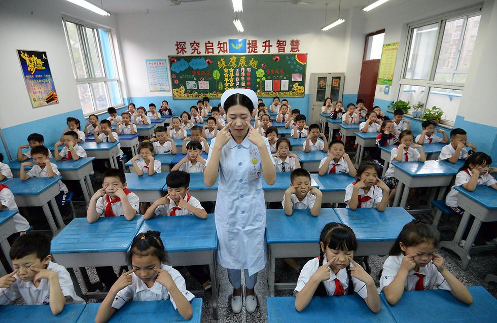 אחות מדגימה לתלמידי בית ספר בהנדאן, סין, כיצד לאמן את העיניים שלהם (צילום: AFP)